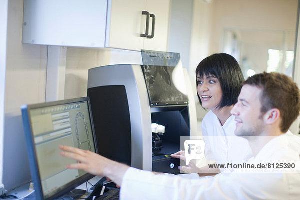 Zahntechniker  die mit dem Computer zahnärztliche Geräte bedienen.