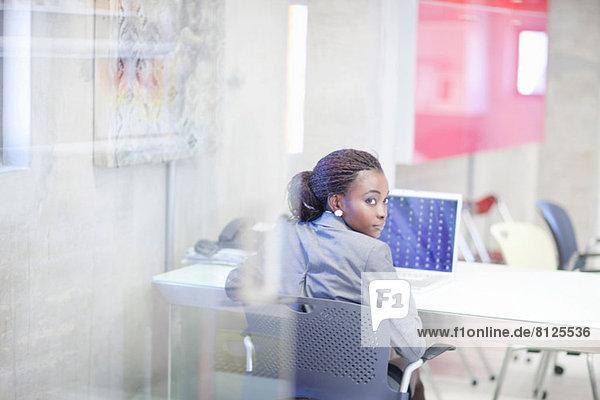 Junge Frau mit Computer im Büro