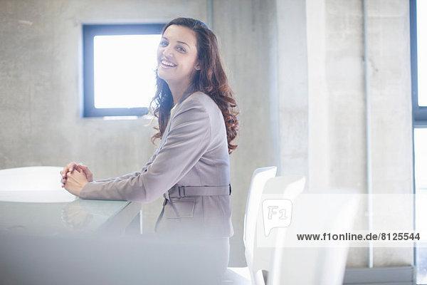 Junge Frau am Vorstandstisch sitzend