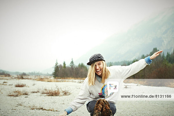 Woman sitting on ground in mountains  laughing