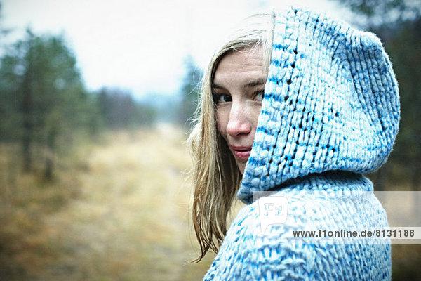 Frau mit Kapuzenoberteil im Wald