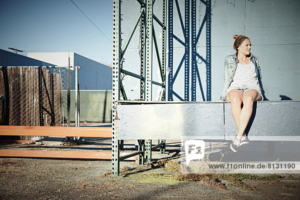 Woman sitting on wall in industrial area