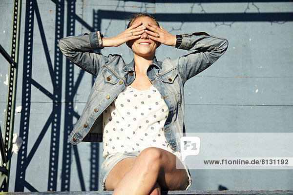 Woman with hands covering eyes