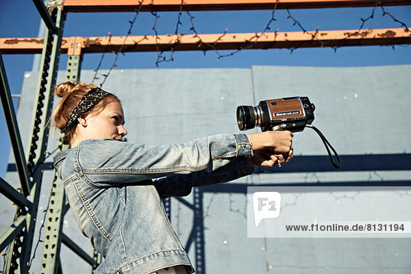 Woman using old video camera to take self portrait