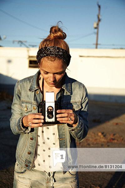 Woman looking at vintage camera