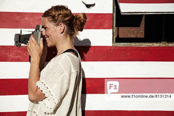 Woman taking photograph using vintage camera