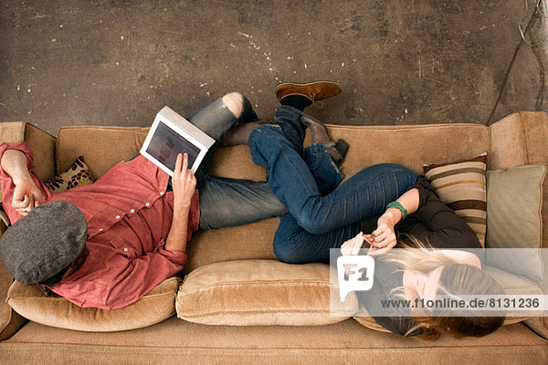 Couple sitting on sofa using digital tablet and smartphone