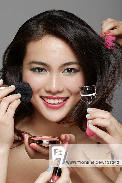 Nahaufnahme des Gesichts der Frau  umgeben von Händen  die Make-up und Beauty-Ausrüstung halten.