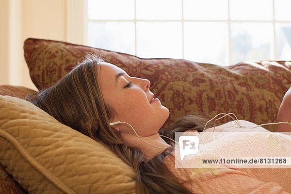 Teenagermädchen auf dem Sofa liegend mit Kopfhörer