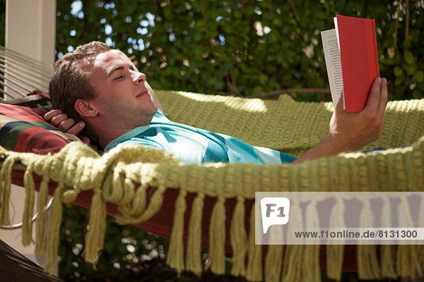 Junger Mann liest Buch in Hängematte