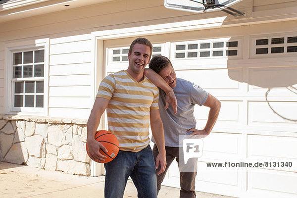 Vater stützt sich auf die Schulter des erwachsenen Sohnes mit Basketball