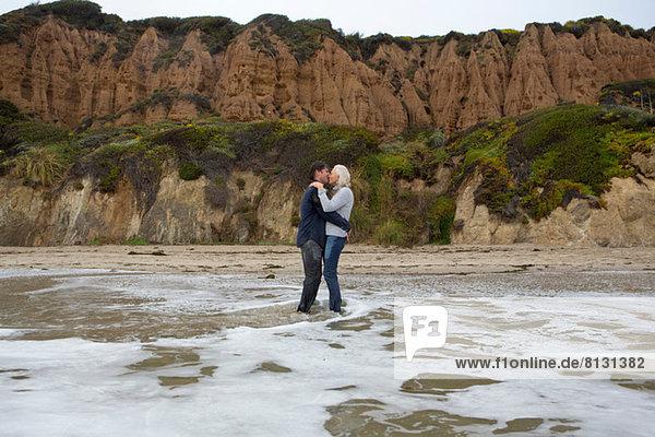 Ein reifes Paar  das im Meer steht und sich küsst.