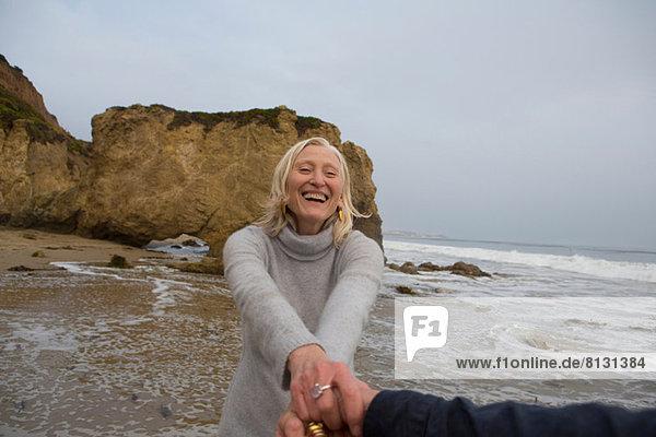 Ein reifes Paar hält sich am Strand an den Händen.