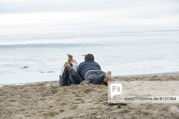 Ein reifes Paar  das am Strand liegt und aufs Meer schaut.