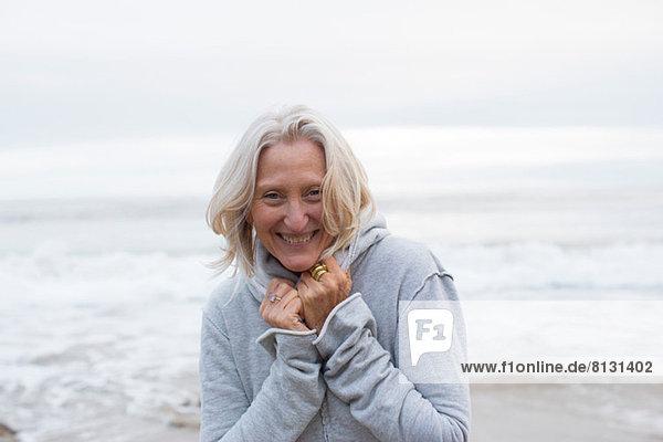 Reife Frau im grauen Pullover am Strand  lächelnd