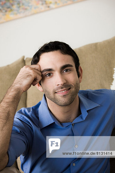 Porträt eines jungen Mannes  der sich auf den Ellenbogen stützt.