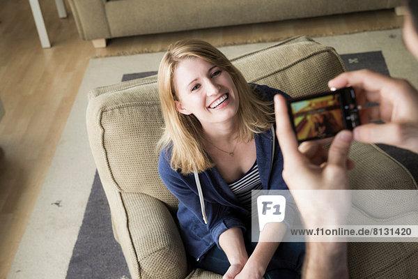 Mann fotografiert junge Frau am Handy
