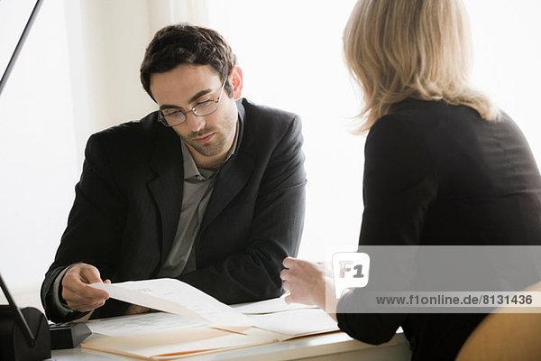 Junge Büroangestellte bei der Suche nach Papierkram