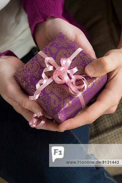 Zwei Personen halten Geschenkschachtel mit rosa Schleife