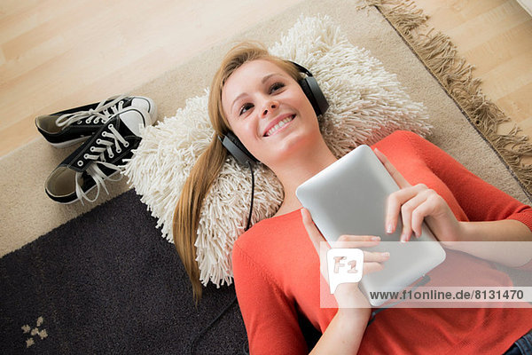 Teenager Mädchen mit Kopfhörer und digitalem Tablett