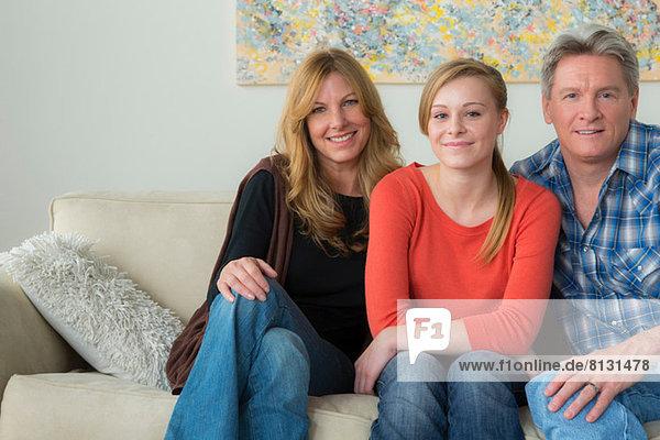 Porträt von Mutter und Vater mit jugendlicher Tochter auf Sofa