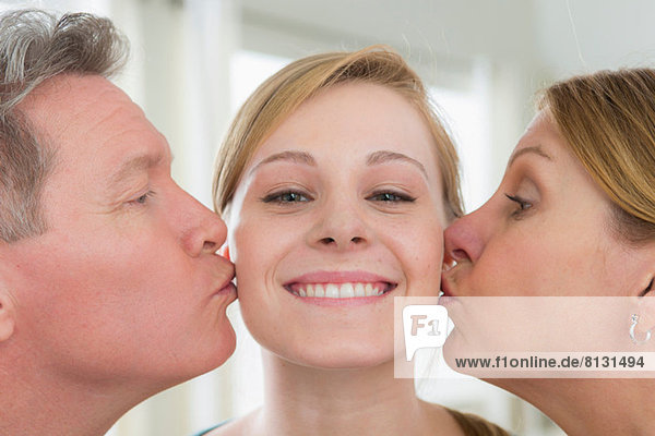 Mutter und Vater küssen Teenager-Tochter auf Wange
