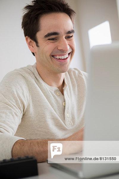 Mid Erwachsene Mann mit Laptop  lachend