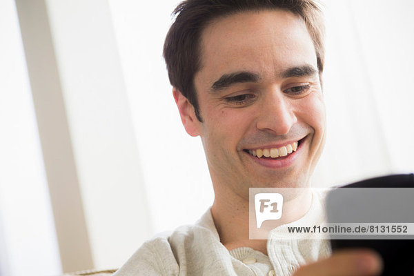 Mittlerer erwachsener Mann mit Handy  lächelnd