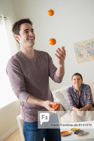 Man juggling oranges  woman watching