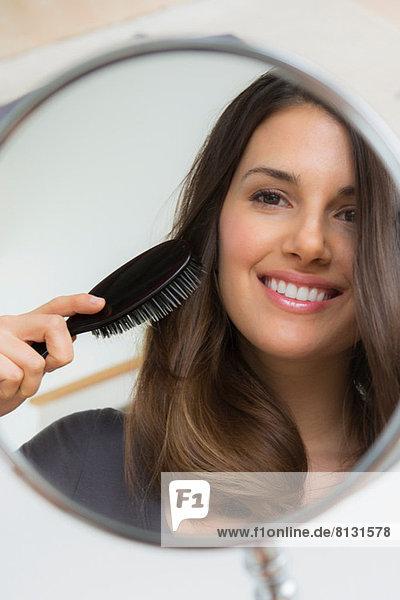Junge Frau bürstet Haare im Spiegel