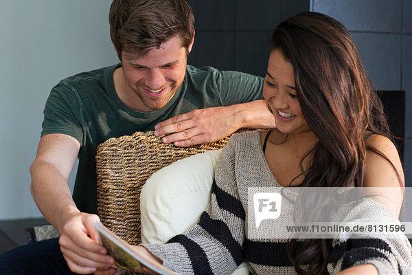 Junges Paar schaut auf die Zeitschrift  lächelnd