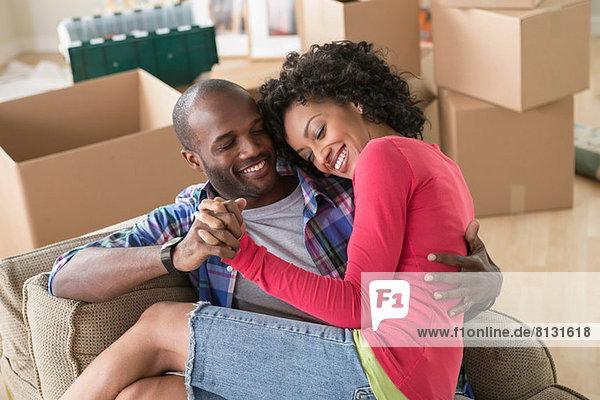Mittleres erwachsenes Paar auf Sessel in neuem Zuhause