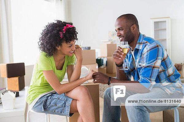 Mittleres erwachsenes Paar in neuem Zuhause mit Champagner
