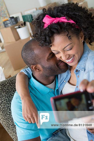 Mittleres erwachsenes Paar  das sich selbst mit Fotohandy fotografiert.