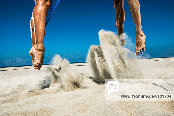 Zwei Beachvolleyballspieler springen in der Luft im Sand.