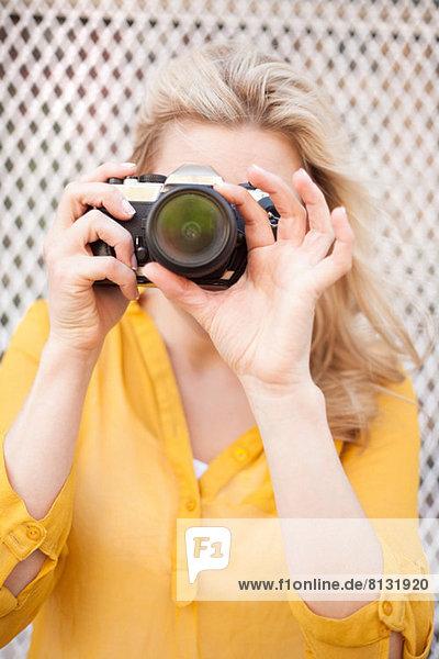 Frau fotografiert mit Kamera