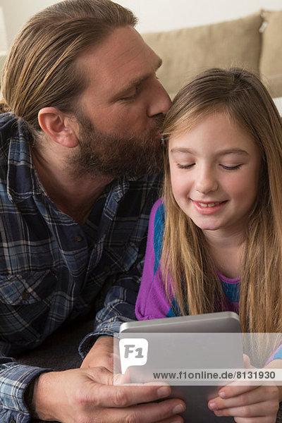 Mädchen beim Betrachten des digitalen Tabletts mit Vater