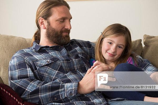 Vater und Tochter plaudern auf der Couch