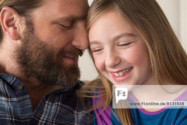 Vater lehnt das Gesicht auf den Kopf der Tochter.
