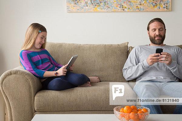 Vater und Tochter sitzen auf der Couch