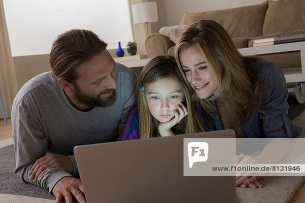 Eltern und Kind schauen auf den Laptop