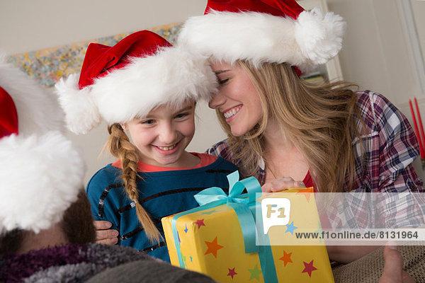 Mädchen schaut auf Weihnachtsgeschenk