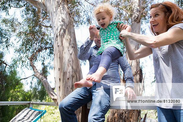 Eltern schwingen das Kind an den Armen