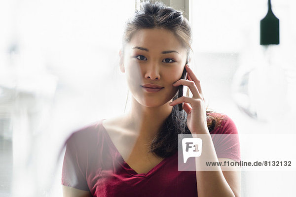 Woman on mobile phone looking at camera
