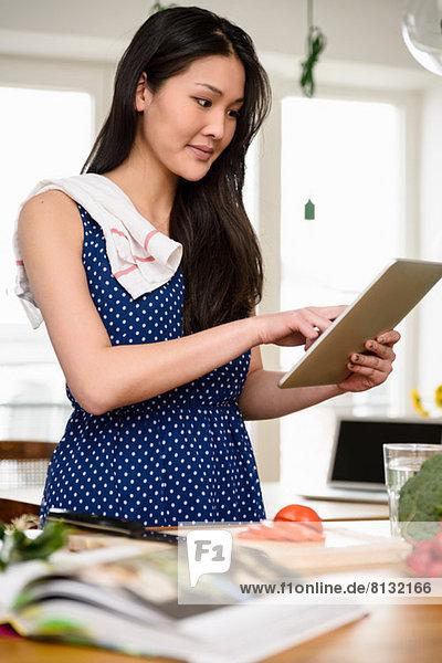 Frau mit Geschirrtuch über der Schulter mit digitalem Tablett