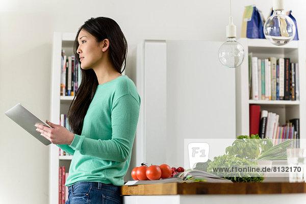 Profil der Frau  die ein digitales Tablett hält  das sich gegen den Tisch lehnt.