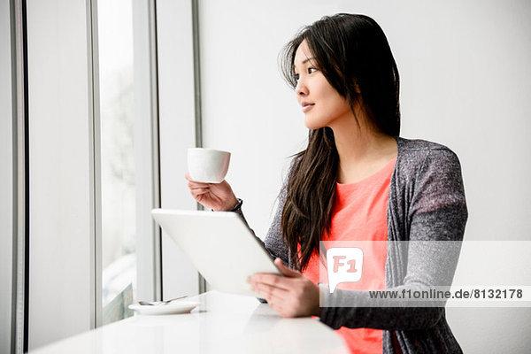 Frau mit digitalem Tablett beim Ausbrechen mit Blick aus dem Fenster