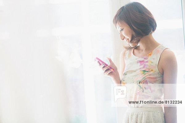 Frau lächelt über SMS auf dem Handy