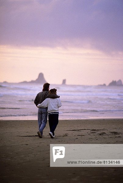 USA  OREGON  CANNON BEACH  COUPLE WALKING ALONG BEACH IN EVENING LIGHT.