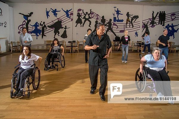 An African American dance teacher instructs handicapped adults perform a wheelchair dance with normal adults in San Diego  CA. The physical benefits of wheelchair dancing include the maintenance of physical balance  flexibility  range of motion  coordination and improved respiratory control. Psychological effects are social interaction and the development of relationships.